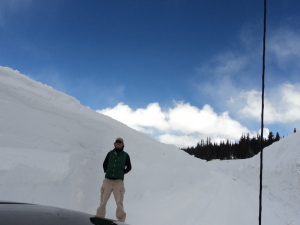 Josh standing against the wall of snow at the road closure from two years ago.